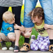 Stock Photo: Siblings holding legs of parents