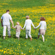 Family walking on flower meadow — Stock Photo