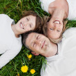 Happy family lying on green grass — Stok fotoğraf