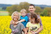 Happy family against flower meadow — Stock Photo