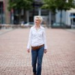 joven y guapa mujer caminando por una calle — Foto de Stock