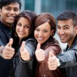 Stock Photo: Four motivated friends giving a thumbs up