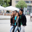 Four friends walking through the city — Stock Photo