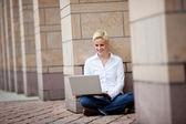 Femme blonde assise avec ordinateur portable — Photo