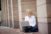 Woman With Laptop Sitting Against Column — Stock Photo