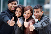 Four motivated friends giving a thumbs up — Stock Photo