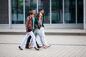 Four Asian friends walking through town — Stock Photo