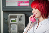 Woman with red hair and pink phone — Stock Photo