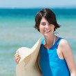 Smiling woman with her sunhat at the seaside — Stock Photo