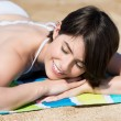 Womrelaxing sunbathing on beach — Stock Photo #27775297