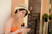 Attractive woman smiling while writing a message — Stock Photo