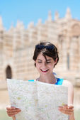 Woman reading a map while on holiday — Stock Photo
