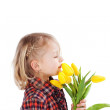 Little blond girl with yellow tulips — Stock Photo #27818717