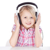 Girl Listening To Music On Headphones While Sitting At Table — Stock Photo