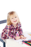 Smiling little girl colouring in her book — Stock Photo