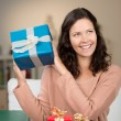 Happy woman guessing the contents of her gifts — Stok fotoğraf