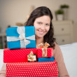 Smiling woman with a stack of gift boxes — Stock Photo