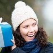 Laughing woman shaking her gift — Stock Photo