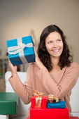 Glad kvinna gissa innehållet i hennes gåvor — Stockfoto