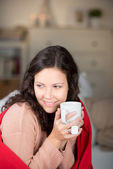 Shivering woman warming herself with hot tea — Stock Photo