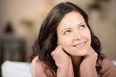 Pensierosa giovane donna alzando in casa — Foto Stock