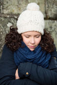 Woman In Winter Clothes Shivering Against Stonewall — Stock Photo
