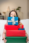 Woman carrying a huge pile of gifts — Stock Photo