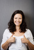 Woman Gesturing Thumbs Up Against Wall — Stock Photo