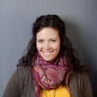 Woman In Winter Clothes Smiling Against Gray Wall — Stock Photo