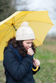 Woman walking under an umbrella coughing — Stock Photo