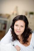 Ev gülümseyen genç bir kadın — Stok fotoğraf