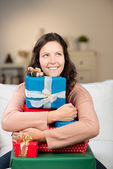 Frau umarmen weihnachtsgeschenke beim wegsehen — Stockfoto