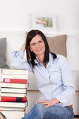 Woman sitting at home with a pile of books — Stock Photo