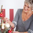 Beautiful senior woman decorating a tree — Stock Photo