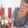 Beautiful senior woman decorating a tree — Stok fotoğraf