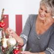 Beautiful senior woman decorating a tree — Stock Photo