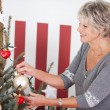 Senior woman hanging Christmas decorations — Stock Photo