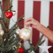 Older woman decorating a Christmas tree — Stock Photo
