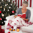 Senior lady reading in front of the Christmas tree — Stock Photo