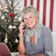 Senior woman chatting on the phone at Christmas — Stock Photo