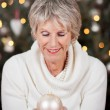 Stylish senior lady with a Christmas bauble — Stock Photo