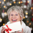 Laughing elderly lady with an Xmas gift voucher — Stock Photo #27948033