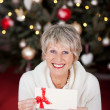 Smiling senior lady with a gift voucher — Stock Photo #27948035