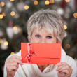 Elderly lady with a red gift voucher — Stock Photo #27948049