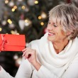 Smiling woman displaying a red Christmas voucher — Stock Photo