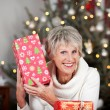 Laughing senior lady with a Christmas gift — ストック写真