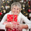 Laughing woman hugging a pile of Christmas gifts — Stock Photo #27948065