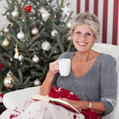 Smiling elderly woman with a cup of tea — Stock Photo