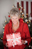Happy beautiful senior with a Christmas gift — Stock Photo