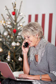 Elderly woman using telephone on Christmas Eve — Stock Photo